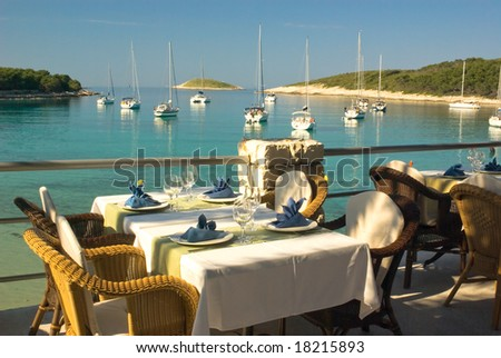 Served tables in beach restaurant near lagoon with yachts - stock photo