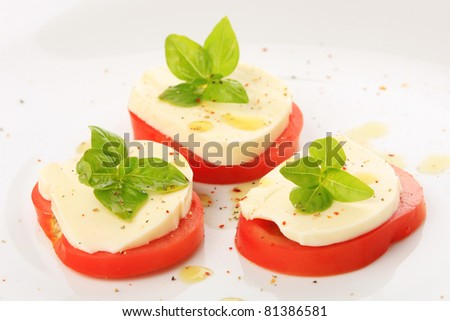 Served tomato with mozzarella and basil on white plate