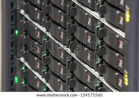 Server rack with multiple hard drives and colored lights. - stock photo