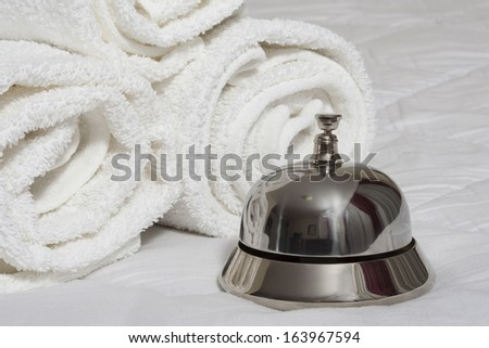 Service bell and rolled towels on bed - stock photo