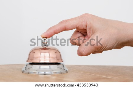 Service Bell. Person using their finger to ring a counter bell. - stock photo
