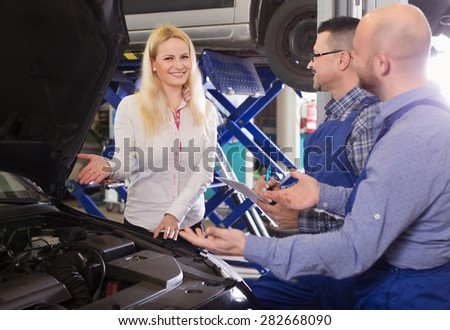 Service crew and happy woman driver standing near car and smiling indoor. Focus on woman