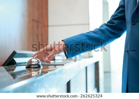 Service, please. Closeup of a businessman hand ringing silver service bell on hotel reception desk - stock photo