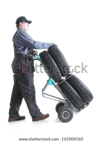 Serviceman carrying a set of four new car tires using hand truck shot on white - stock photo