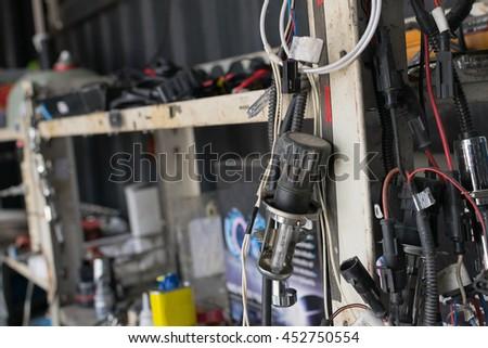 Serviceman checking headlight in a car at garage - stock photo