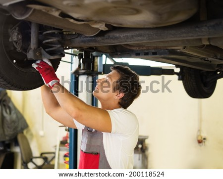Serviceman checking suspension in a car workshop  - stock photo