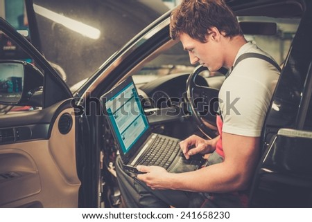 Serviceman making car diagnostics with laptop in a workshop - stock photo