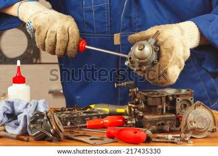 Serviceman repairing parts of the engine in the workshop - stock photo