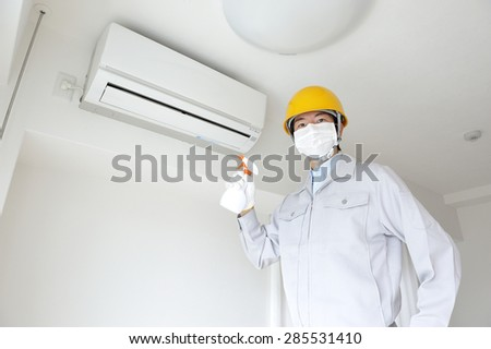 Serviceman wearing the work clothes to inspect air conditioning in the home