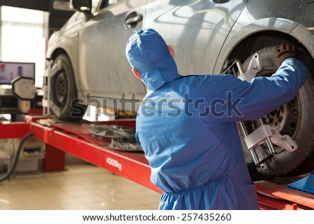 Serviceman worker checking car wheel with computerized alignment device in automobile service station - stock photo