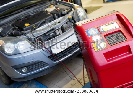 Servicing car air conditioner in vehicle service or repair workshop - stock photo