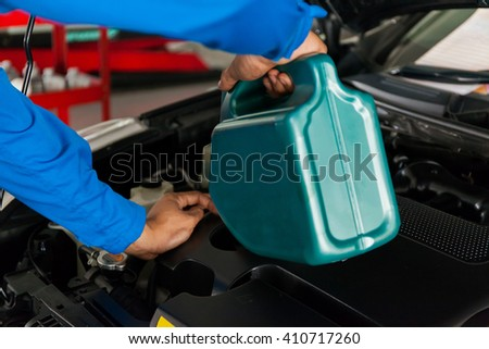 Servicing mechanic pouring new oil lubricant into the car engine - stock photo