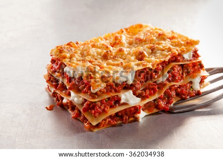 Serving a portion of Italian beef lasagne with mozzarella cheese on a metal spatula over a scratched textured white background - stock photo