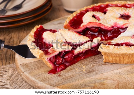 Serving a slice of cherry pie on a wooden platter