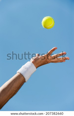 Serving ball. Close-up of male hand in wristband throwing tennis ball against blue sky