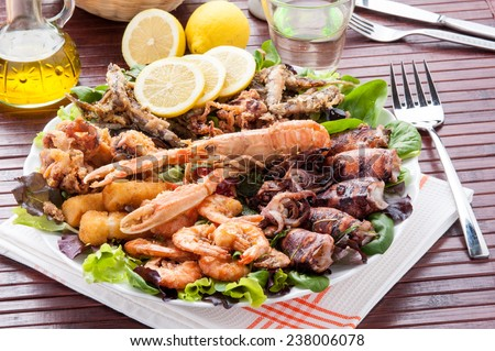 Serving dish with mixed fried fish and shellfish - stock photo