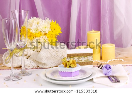Serving fabulous wedding table in purple and yellow color on white and purple fabric background - stock photo