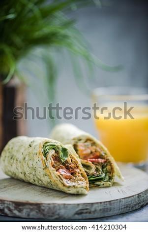 serving healthy breakfast, wrap and orange juice - stock photo