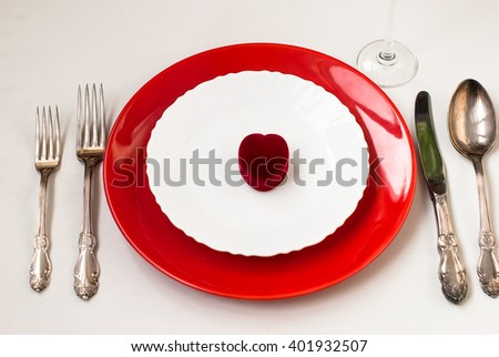 Serving holiday table, spoon, fork, knife, white and red plates and decor heart on a white table. dinner. holiday valentine