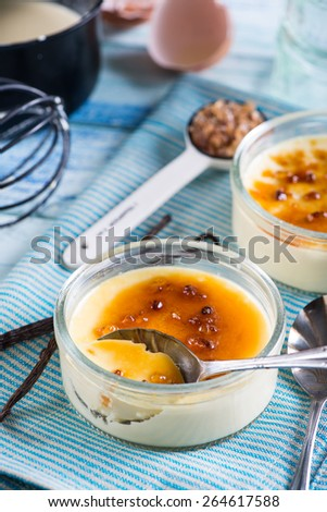 serving homemade creme brulee with cane sugar and fresh vanilla - stock photo