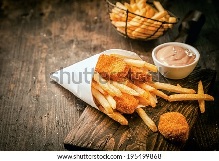 Serving in a paper cone of takeaway crumbed fried fish nuggets with potato chips and a small bowl of sauce or dip on a rustic wooden table with copyspace - stock photo