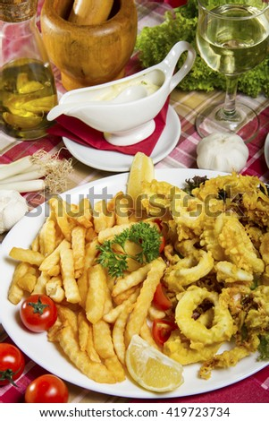 Serving of breaded and deep-fried calamari and fries on a white plate served on a table with dressing sauce, edible oil and a glass of white wine. - stock photo