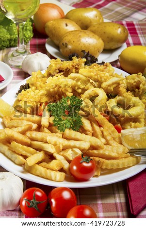 Serving of breaded and deep-fried calamari and fries on a white plate served on a table with fresh vegetables. - stock photo