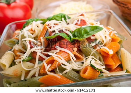 serving of colored penne pasta with tomato sauce and basil - stock photo