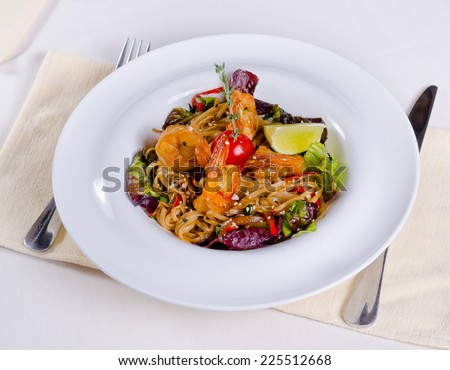 Serving of delicious gourmet savory seafood pasta with prawns and roast fresh vegetables garnished with lemon, high angle view - stock photo