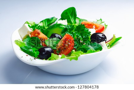 Serving of fresh Greek salad with leafy greens, herbs, tomato, feta and olives on a white background - stock photo