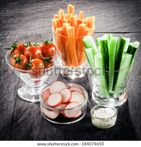 Serving of fresh vegetable crudites on a buffet with individual glass containers of carrot and cucumber batons, sliced radish and cherry tomato with a vinaigrette dip - stock photo