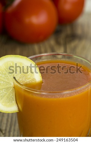 Serving of freshly squeezed tomato and vegetable juice blend garnished with a slice of fresh lemon and served in a glass tumbler on a napkin - stock photo