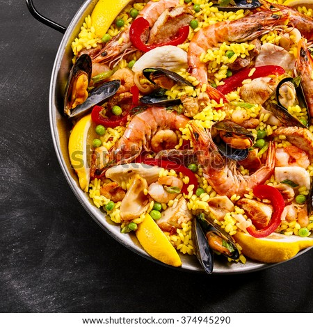 Serving of gourmet seafood paella with pink prawns, mussels, fish, peas, saffron rice and slices of tangy fresh lemon for flavoring in a metal dish, overhead view in square format - stock photo