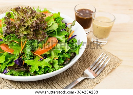Serving of healthy vegetables salad and dressing on wood background. - stock photo