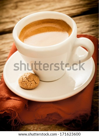 Serving of hot aromatic morning espresso coffee served in a plain white cup with a macaroon on a rustic cloth and old grungy textured wood table