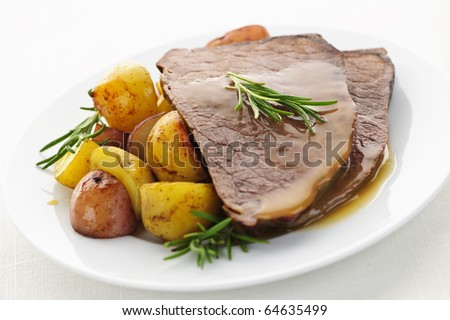 Serving of roast beef and roasted potatoes meal - stock photo