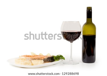 Serving of salmon and red wine in a wine glass with an unlabelled bottle alongside - stock photo