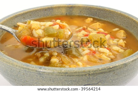 Serving of spicy chicken soup in stoneware bowl with spoon - stock photo