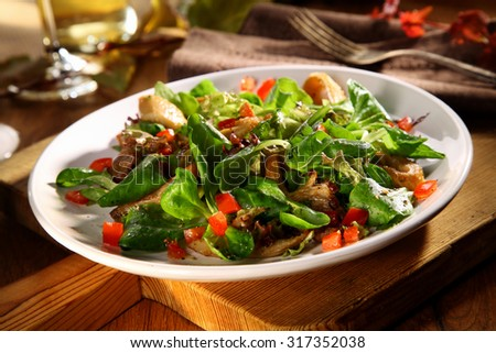 Serving of tasty King Oyster salad with cold grilled mushrooms, rocket, tomato and lettuce for a healthy autumn snack or appetizer - stock photo