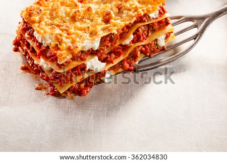 Serving of tasty traditional Italian lasagne with layers of noodles and minced beef with cheese on a spatula, copy space on a textured white surface below - stock photo