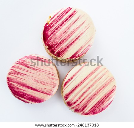 serving of three french macaroons on a white background - stock photo