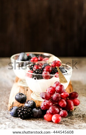 Serving of white Yogurt with Whole Fresh Blueberries  on Old Rustic Wooden Table. Closeup Detail. - stock photo