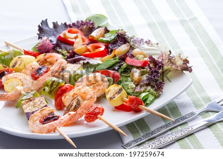 Serving on a plate of three gourmet shrimp skewers or kebabs with salad greens, tomato and sweet pepper , low angle close up on a dinner table - stock photo
