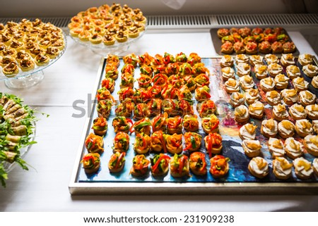 Serving plates and tray with different types of canapes for event - stock photo