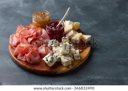 Serving platter with bacon,  cheese and sauce on a dark background, selective focus - stock photo
