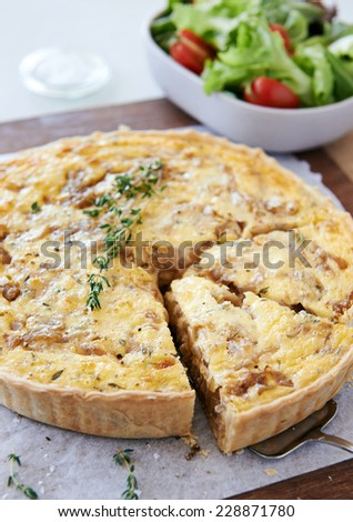 Serving slice of baked quiche tart with caramelised onions and cheese served with side salad - stock photo