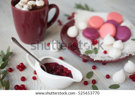 Serving table: cacao with marshmallow, berry jam and macaroons.