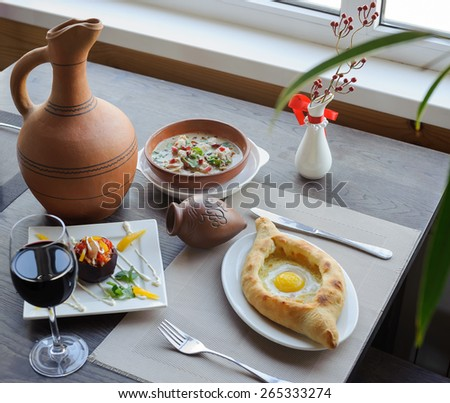 serving table, traditional dish of georgian cuisine, khachapuri, a soup, a jug of wine - stock photo