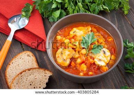 Serving vegetarian stew with chickpeas, mushrooms and pumpkin, horizontal - stock photo