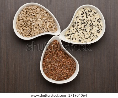 Sesame,flax and sunflower seeds in white bowl - stock photo